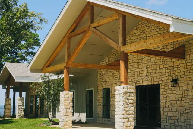 Exterior of stone and beam meeting room overlooking the lake