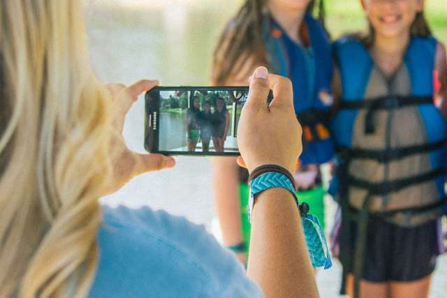 Girl takes photo of campers on a dock with her phone