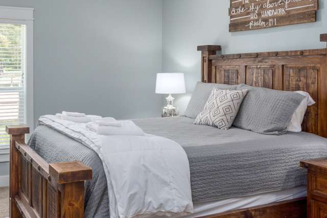 Rustic hotel-style room with queen bed and bunk beds