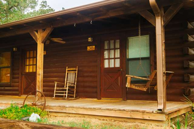 Rustic hotel-style cabin with front porch swings