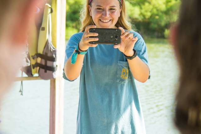 Girl takes a photo with a phone of campers on a dock