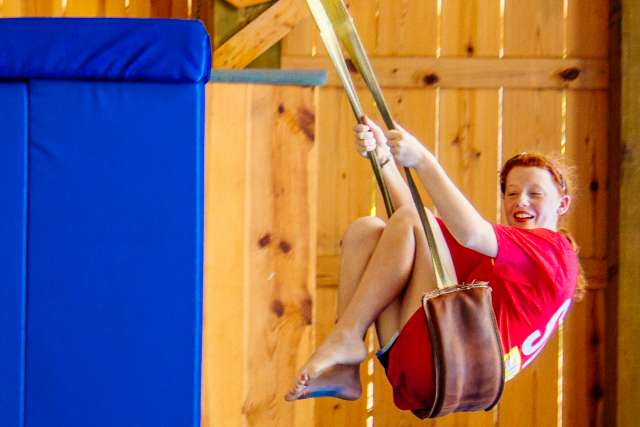 a girl enjoying a ride on the barn swing
