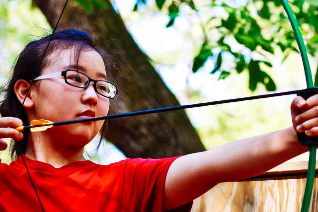 middle school girl taking aim at the archery range