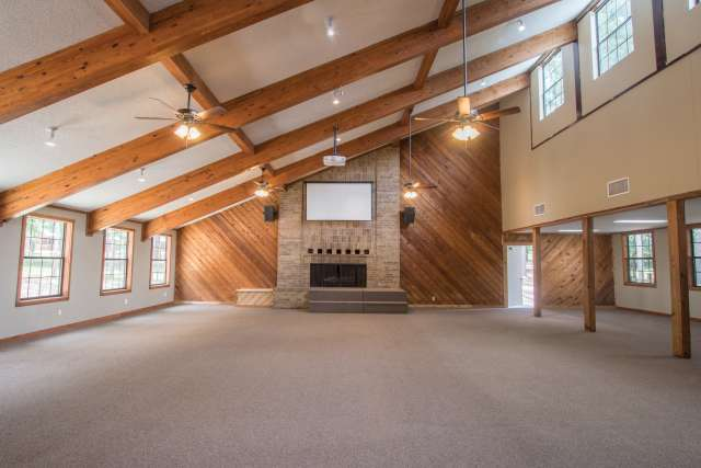 Well-lit meeting room with fireplace and exposed beams on ceiling.