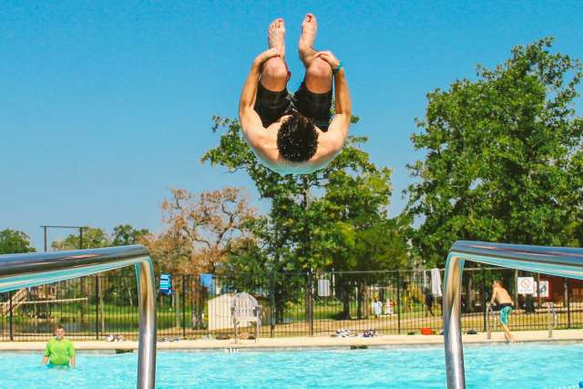 High school boy jumping of diving board
