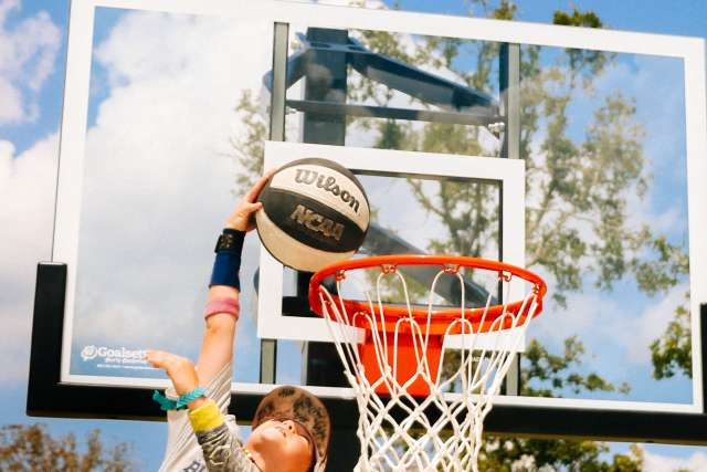 Camper doing a dunk on the basketball court
