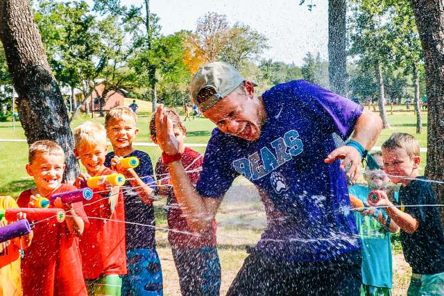 Campers soaking a couselor with water guns