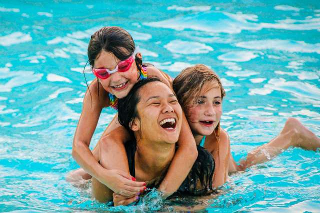 camp counselor and campers laughing in the pool