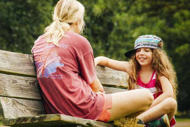 summer camp counselor talking with a camper on a bench