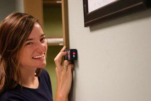 Architect intern smiles while using a laser level