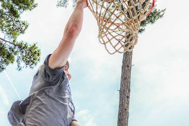 A boy makes a slam dunk in an outdoor game of basketball