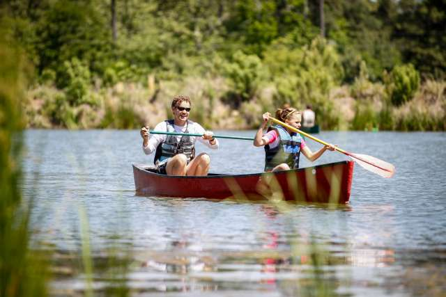 Father and daughter paddle out on the lake in a canoe