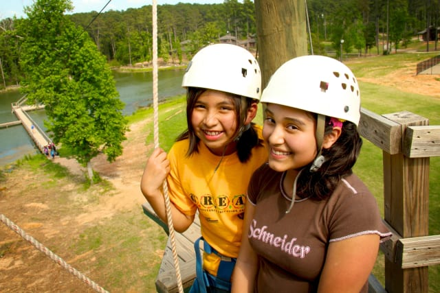 Two girls smile at the top of the zip tower.