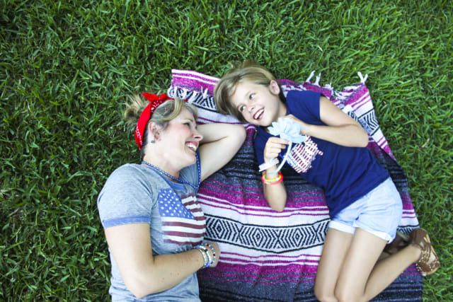 Mom and daughter lie on a blanket in the grass at a picnic