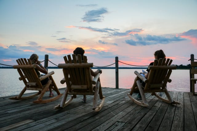 Three ladies sit in rocking chairs on the dock at sunset