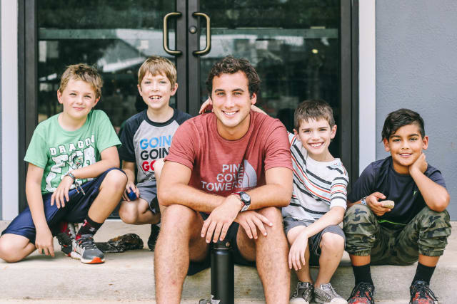 Counselor and group of boys smile together
