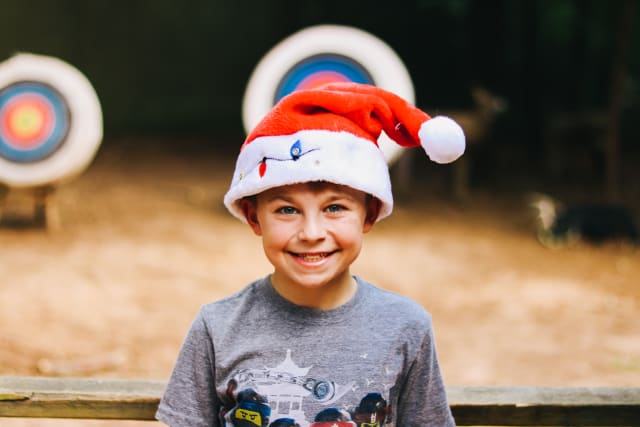 Camper smiling and wearing Santa hat
