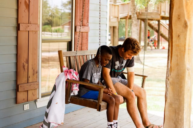 A camper and counselor pray together on a cabin swing