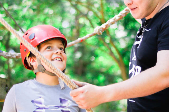 A camper and counselor experience the ropes course together