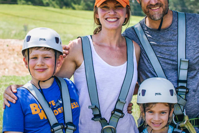 A family smiles after going off the zipline