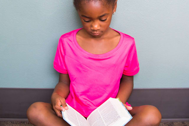 a camper reading the Bible at day camp