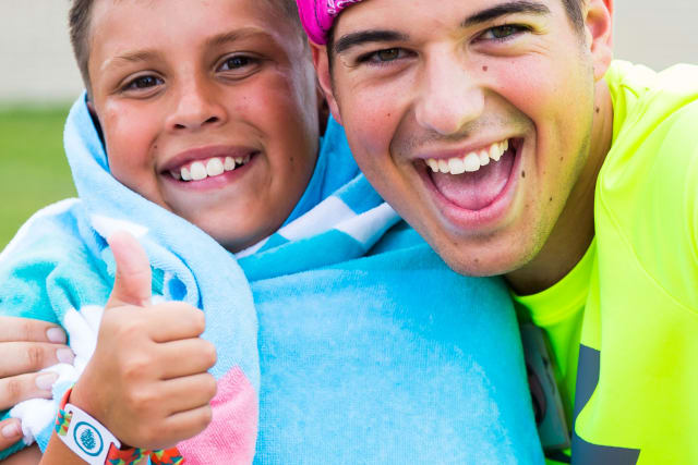 camp counselor and camper giving a thumbs up after a water activity