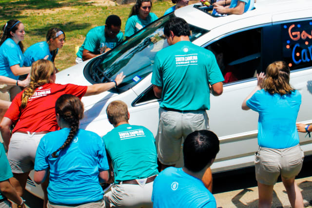 staff greeting cars on opening day at camp