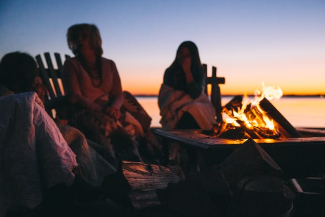 A group of women wrapped in blankets enjoy the sunset around a campfire
