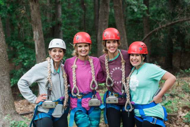 A smiling group of ladies with rope gear about to take on the zip line!