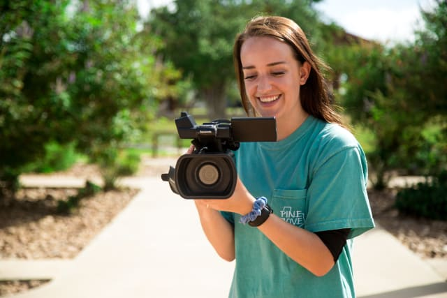 Girl, smiling, looks through video camera
