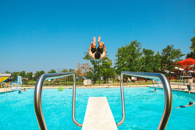 Boy flips off the diving board into the pool