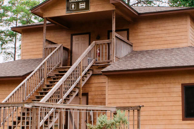 Two-story cabin surrounded by East Texas pine trees