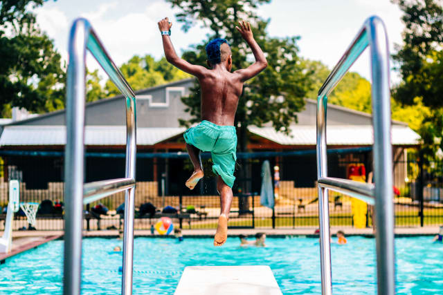 Camper jumping off the diving board at the Towers camp.
