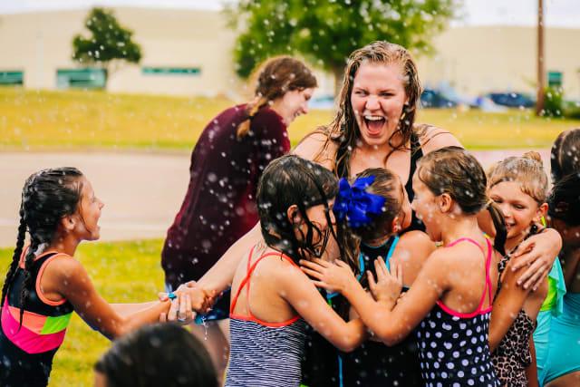camper girls playing with their counselor in the water