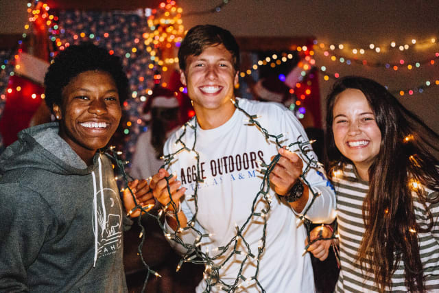 Campers smiling and holding Christmas lights
