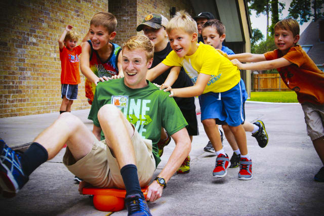 elementary-aged boys pushing a camp counselor on a scooter
