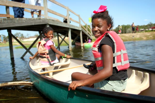 Two girls go for a canoe ride on a sunny day.