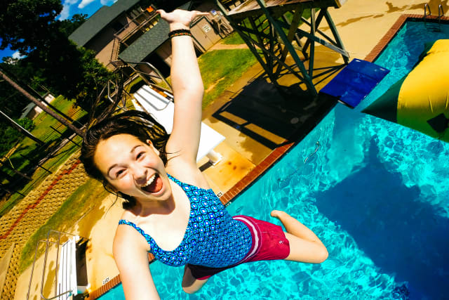 high school girl with a huge smile as she jumps into the pool