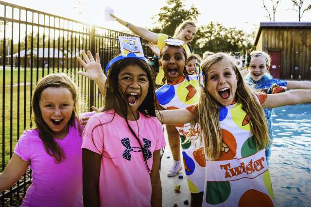 Group of girls dressed up in game board costumes make silly faces for the camera.