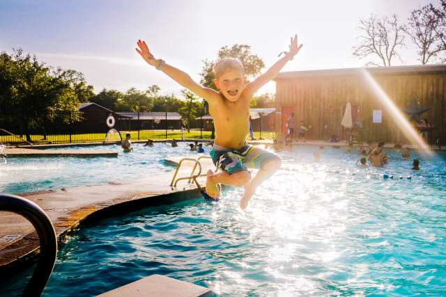 elementary-age boy jumping into the pool
