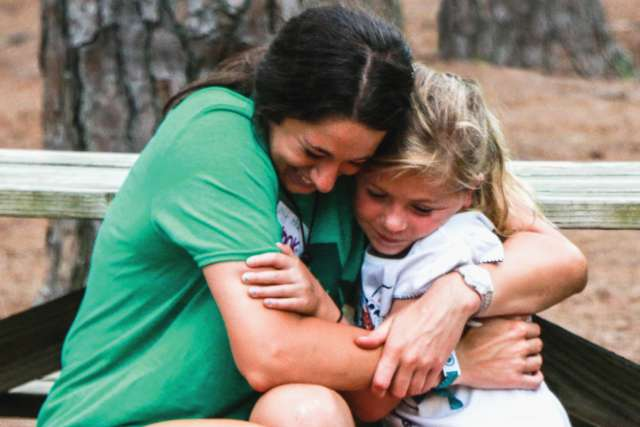 Girl counselor and camper hug on a picnic table.