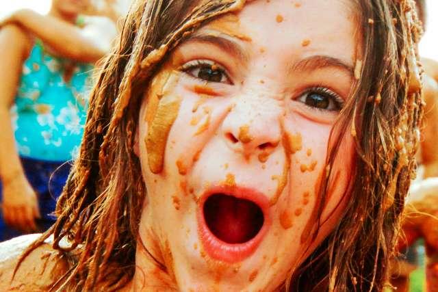 girl having a blast at the very muddy Buffalo Hunt activity