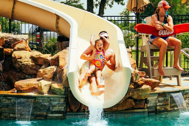 father and daughter on the water slide at the pool