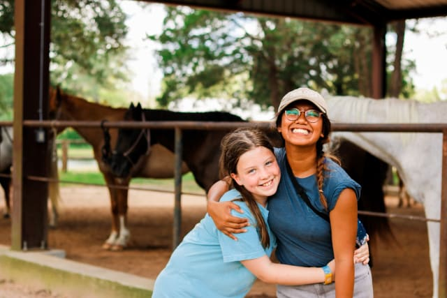 girl camper and girl counselor hugging
