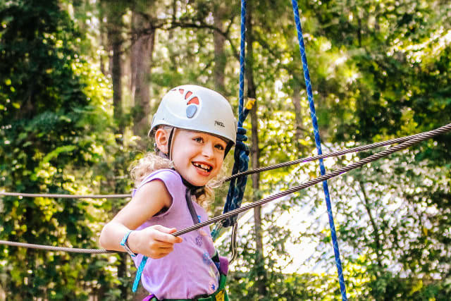 girl smiling on the ropes course