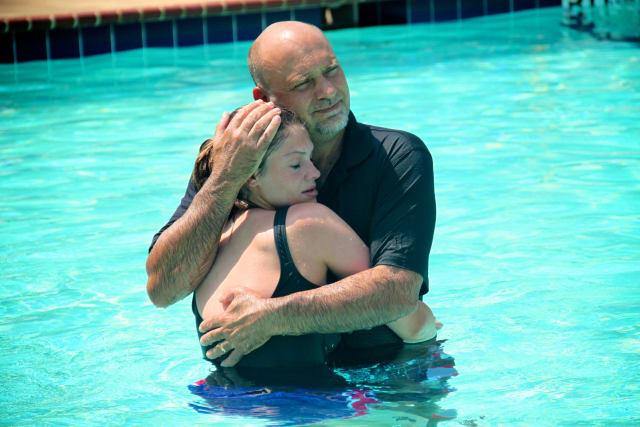 Father hugging daughter in pool