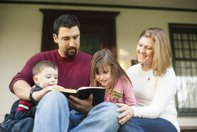 family reading on porch