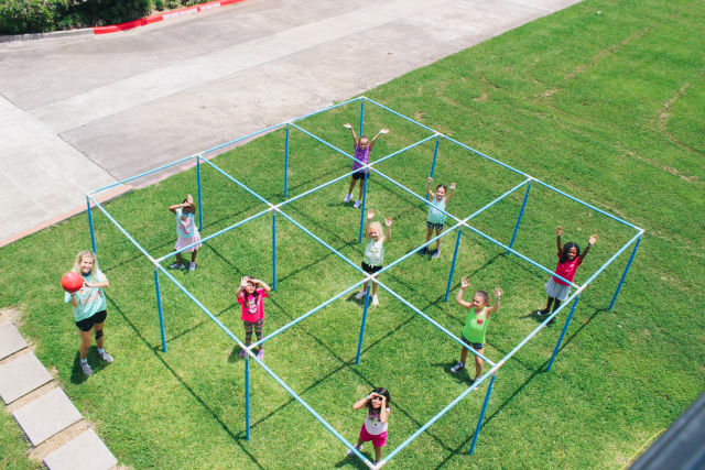 A drone shot of girls playing 9-square and their counselor holding the ball
