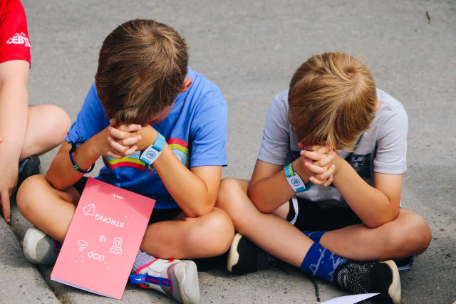 Two boys pray together with their heads bowed and hands folded