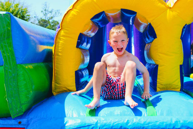 A boy slides through a water inflatable tunnel with a big smile on his face